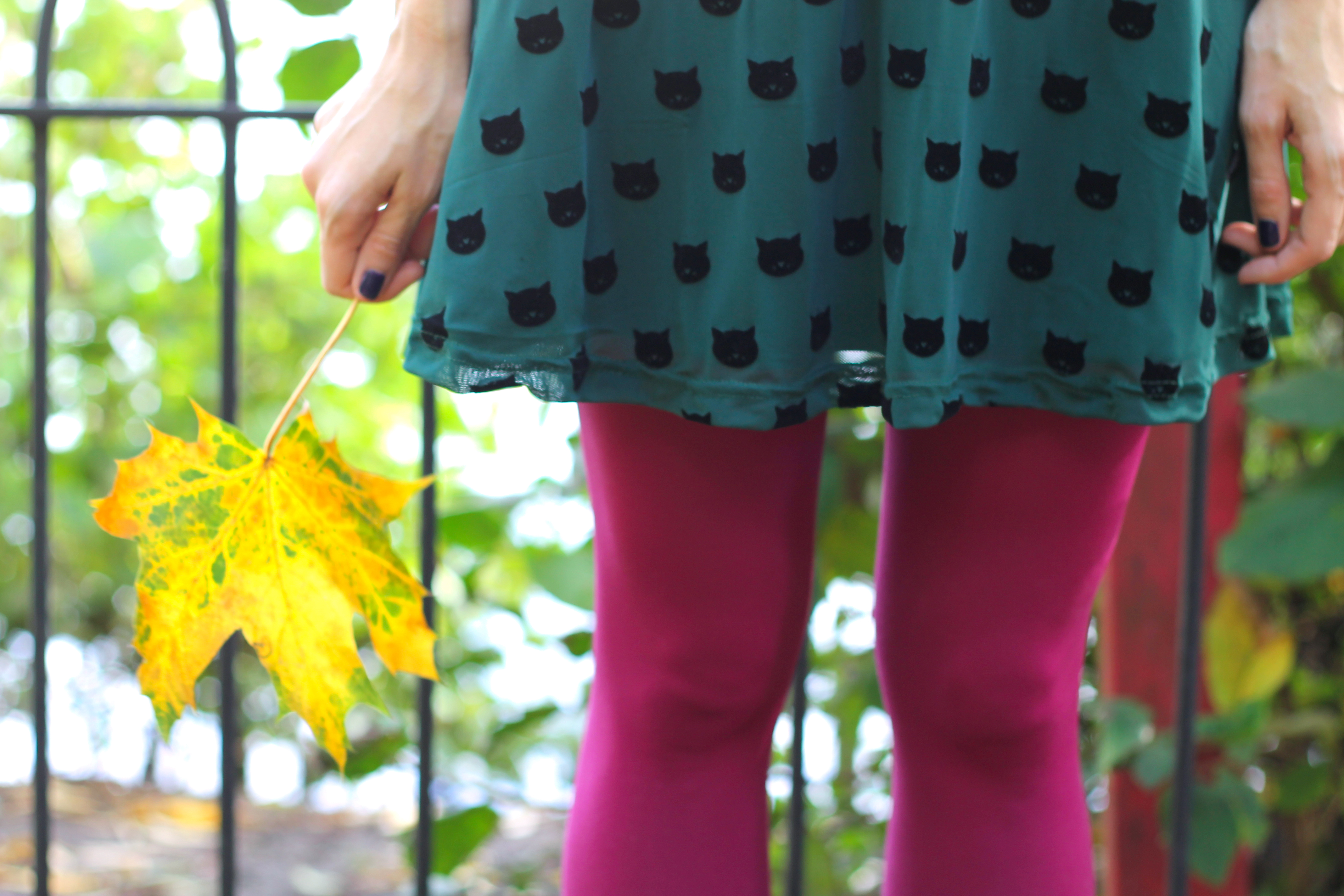 girl in pink tights and a green dress holding a yellow leaf